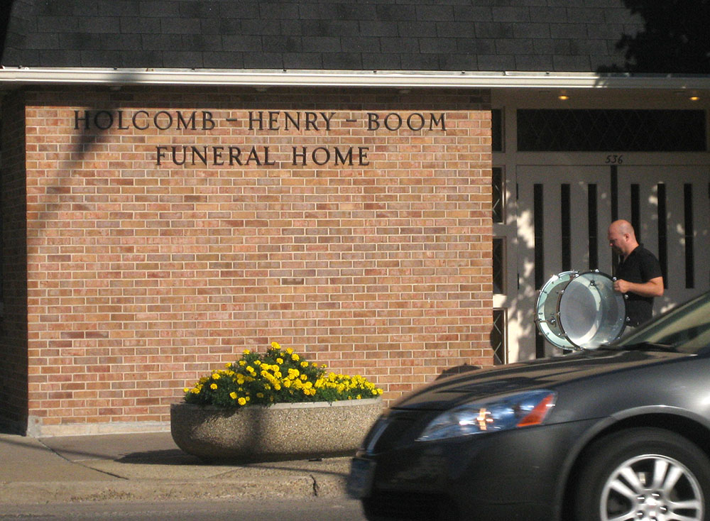 Bass drum player walks past the Holcomb-Henry-Boom Funeral Home.