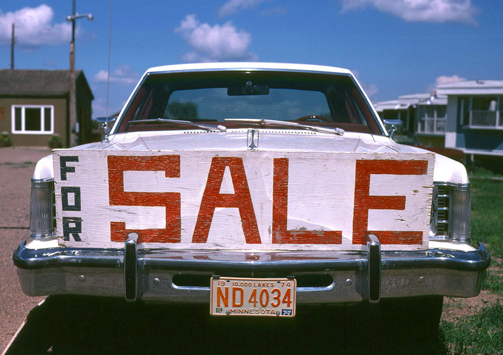 Photo of a large amateur-made 'for sale' sign on the front bumper of a car