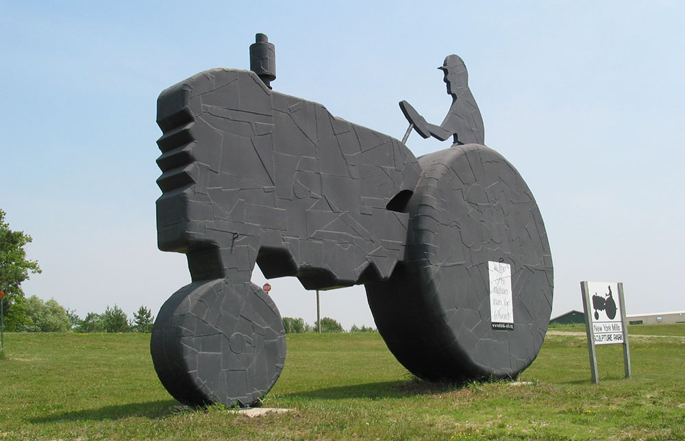 Photo of a large outdoor metal sculpture in the shape of a silhouette of a farmer on a tractor